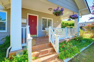 Grey house porch with red door white railings and purple flowers.