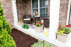 Mulching flowerbeds around the house with a freshly mulched bed alongside an open-air patio decorated with ornamental flowers