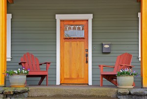 Mission style Stained wood front door with beveled glass surrounded by two Adirondack chairs and flowers